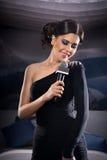 Όμορφο τραγουδώντας κορίτσι Γυναίκα ομορφιάς με το μικρόφωνο Πρότυπος τραγουδιστής γοητείας Στοκ Φωτογραφίες