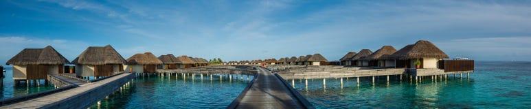 Όμορφο τροπικό πανόραμα παραλιών των bungalos νερού με τη γέφυρα κοντά στον ωκεανό στις Μαλδίβες Στοκ Φωτογραφίες