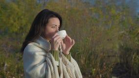 Όμορφο τσάι κατανάλωσης γυναικών στην ανατολή που τυλίγεται σε ένα καρό φιλμ μικρού μήκους