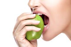 Όμορφο υγιές στόμα που δαγκώνει τη μεγάλη πράσινη Apple Στοκ Εικόνες