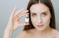 Όμορφο υγρό νεολαίας μπουκαλιών φαρμάκων δερμάτων γυναικών στοκ φωτογραφία με δικαίωμα ελεύθερης χρήσης