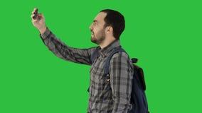 Όμορφο φέρνοντας σακίδιο πλάτης νεαρών άνδρων και λήψη μιας εικόνας του σε μια πράσινη οθόνη, κλειδί χρώματος απόθεμα βίντεο