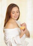 Όμορφο φρέσκο νέο κορίτσι που φορά το άσπρο μπουρνούζι που εφαρμόζει την κρέμα Στοκ Φωτογραφία