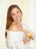 Όμορφο φρέσκο νέο κορίτσι που φορά το άσπρο μπουρνούζι που εφαρμόζει την κρέμα Στοκ φωτογραφία με δικαίωμα ελεύθερης χρήσης