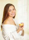 Όμορφο φρέσκο νέο κορίτσι που φορά το άσπρο μπουρνούζι που εφαρμόζει την κρέμα Στοκ Εικόνα