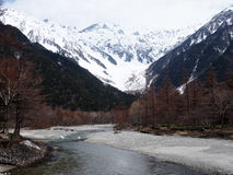Όμορφο φυσικό τοπίο με τον ποταμό και βουνά που καλύπτονται με το χιόνι Στοκ Φωτογραφία