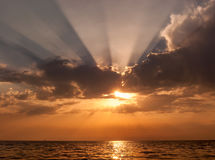 Όμορφο φυσικό seascape ηλιοβασιλέματος με τον ήλιο που τιτιβίζει έξω από πίσω από την παραγωγή σύννεφων ακτινοβολώντας sunrays κα Στοκ Εικόνες