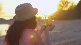 Όμορφο φυσώντας κομφετί γυναικών σε σε αργή κίνηση στην παραλία Ο ευτυχής φυσώντας χρυσός έφηβη ακτινοβολεί μακριά παραδίδει φιλμ μικρού μήκους