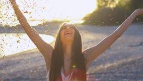 Όμορφο φυσώντας κομφετί γυναικών σε σε αργή κίνηση στην παραλία Ο καυκάσιος ευτυχής φυσώντας χρυσός έφηβη ακτινοβολεί μακριά απόθεμα βίντεο
