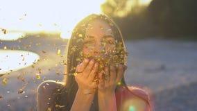 Όμορφο φυσώντας κομφετί γυναικών σε σε αργή κίνηση στην παραλία Ο καυκάσιος ευτυχής φυσώντας χρυσός έφηβη ακτινοβολεί μακριά φιλμ μικρού μήκους
