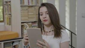 Όμορφο χαλαρωμένο κορίτσι στη μουσική της βιβλίων και ακούσματος ανάγνωσης δωματίων ή audiobook - απόθεμα βίντεο