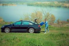 Όμορφο χαμογελώντας άτομο που πηγαίνει στις διακοπές, που φορτώνουν τη βαλίτσα του στον κορμό αυτοκινήτων στοκ φωτογραφία με δικαίωμα ελεύθερης χρήσης