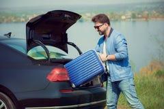 Όμορφο χαμογελώντας άτομο που πηγαίνει στις διακοπές, που φορτώνουν τη βαλίτσα του στον κορμό αυτοκινήτων στοκ εικόνα με δικαίωμα ελεύθερης χρήσης
