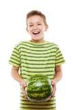 Όμορφο χαμογελώντας αγόρι παιδιών που κρατά τα πράσινα φρούτα καρπουζιών στοκ φωτογραφία