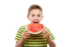 Όμορφο χαμογελώντας αγόρι παιδιών που κρατά την κόκκινη φέτα φρούτων καρπουζιών στοκ φωτογραφία