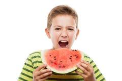 Όμορφο χαμογελώντας αγόρι παιδιών που κρατά την κόκκινη φέτα φρούτων καρπουζιών στοκ φωτογραφία με δικαίωμα ελεύθερης χρήσης