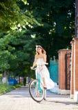 Όμορφο χαμογελώντας θηλυκό που οδηγά το μπλε ποδήλατο κάτω από την πράσινη αλέα πάρκων Στοκ εικόνα με δικαίωμα ελεύθερης χρήσης