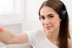 Όμορφο χαμογελώντας κορίτσι στα ακουστικά που κάνει selfie, μακρυμάλλες brunette στα άσπρα ενδύματα, κινηματογράφηση σε πρώτο πλά Στοκ Φωτογραφία