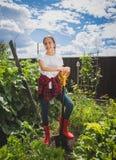 Όμορφο χαμογελώντας κορίτσι στις λαστιχένιες μπότες που σκάβουν το χώμα στον κήπο Στοκ Εικόνα