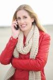 Όμορφο χαμογελώντας ξανθό κορίτσι στο τηλέφωνο Στοκ Φωτογραφίες