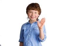 Όμορφο χαμογελώντας αγόρι που κυματίζει με το χέρι του Στοκ Φωτογραφία
