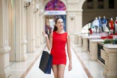 Όμορφο χαμογελώντας κορίτσι σε ένα κόκκινο φόρεμα, που κρατά τις τσάντες αγορών Στοκ Φωτογραφία