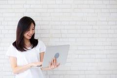Όμορφο χαμόγελο γυναικών πορτρέτου ασιατικό νέο που χρησιμοποιεί το lap-top που στέκεται στον εργασιακό χώρο στο συγκεκριμένο υπό στοκ φωτογραφία με δικαίωμα ελεύθερης χρήσης