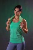 Όμορφο χαμόγελο αθλητικό, στάση γυναικών ικανότητας, που θέτει με μια πετσέτα σε ένα γκρίζο υπόβαθρο με ένα πράσινο backlight Στοκ Εικόνα