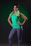 Όμορφο χαμόγελο αθλητικό, στάση γυναικών ικανότητας, που θέτει με μια πετσέτα σε ένα γκρίζο υπόβαθρο με ένα πράσινο backlight Στοκ Φωτογραφία