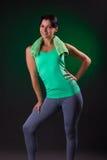 Όμορφο χαμόγελο αθλητικό, στάση γυναικών ικανότητας, που θέτει με μια πετσέτα σε ένα γκρίζο υπόβαθρο με ένα πράσινο backlight Στοκ εικόνες με δικαίωμα ελεύθερης χρήσης