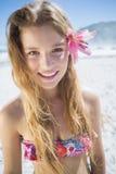 Όμορφο χαμόγελο ξανθό με το εξάρτημα τρίχας λουλουδιών στην παραλία Στοκ Φωτογραφίες