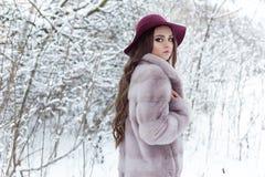 Όμορφο χαριτωμένο κομψό κορίτσι σε ένα παλτό και ένα καπέλο γουνών που περπατούν το χειμερινό δασικό φωτεινό παγωμένο πρωί Στοκ Φωτογραφία