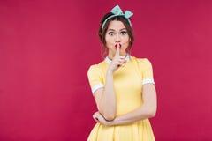 Όμορφο χαριτωμένο κορίτσι pinup στο κίτρινο φόρεμα που παρουσιάζει σημάδι σιωπής Στοκ εικόνες με δικαίωμα ελεύθερης χρήσης