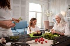 Όμορφο χαριτωμένο μικρό κορίτσι που συμμετέχει στο μαγειρεύοντας μεσημεριανό γεύμα γιαγιάδων της Στοκ φωτογραφία με δικαίωμα ελεύθερης χρήσης