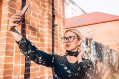 Όμορφο χαριτωμένο ξανθό πρότυπο στην τοποθέτηση φορεμάτων στην πόλη στοκ φωτογραφία