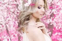 Όμορφο χαριτωμένο τρυφερό νέο ξανθό κορίτσι στη φυτεία με τριανταφυλλιές στα ανθίζοντας δέντρα στα ευγενή μυθικά χρώματα Στοκ Εικόνα