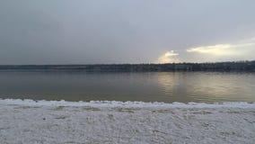 Όμορφο χειμερινό βράδυ στην αμμώδη παραλία του ποταμού πτώση νιφάδων χιονιού στο νερό απόθεμα βίντεο
