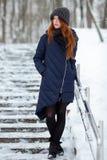 Όμορφο χειμερινό πορτρέτο της νέας λατρευτής redhead γυναίκας το χαριτωμένο πλεκτό χειμώνα καπέλων που έχει τη διασκέδαση στο χιο Στοκ Εικόνα