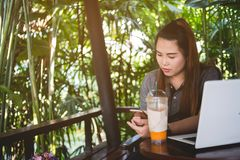 Όμορφο χρησιμοποιημένο γυναίκα smartphone, lap-top και παγωμένο τσάι στον πίνακα στοκ φωτογραφίες με δικαίωμα ελεύθερης χρήσης