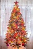 Όμορφο χριστουγεννιάτικο δέντρο με τις ζωηρόχρωμες διακοσμήσεις, και τεράστιο κόκκινο αστέρι στην κορυφή Στοκ Εικόνες