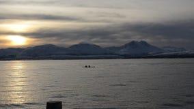 Όμορφο χρυσό ηλιοβασίλεμα πέρα από το δυνατό χιονώδες τοπίο βουνών με το relfection στη σαφή επιφάνεια φιορδ με τα paddlers kajaq φιλμ μικρού μήκους