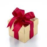 Όμορφο χρυσό παρόν κιβώτιο με το κόκκινες τόξο και τις κορδέλλες Στοκ Φωτογραφία
