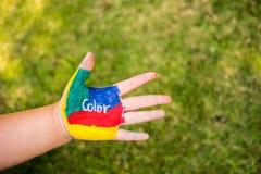 Όμορφο χρωματισμένο χέρι θηλυκό σε ένα πράσινο υπόβαθρο χλόης Στοκ φωτογραφίες με δικαίωμα ελεύθερης χρήσης