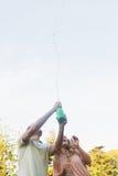 Όμορφο ψεκάζοντας μπουκάλι ατόμων της σαμπάνιας με τον ξανθό συνεργάτη στοκ εικόνες