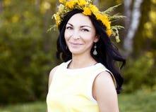 Όμορφο ύφος μόδας γυναικών brunette υπαίθρια στο κίτρινο φόρεμα που χαμογελά την ευτυχή ανθοδέσμη ιδέας έννοιας στο κεφάλι της Στοκ Εικόνα