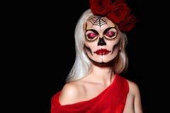 Όμορφο ύφος σύνθεσης αποκριών Ξανθό πρότυπο κρανίο Makeup ζάχαρης ένδυσης με τα κόκκινα τριαντάφυλλα Έννοια Muerte Santa στοκ φωτογραφίες