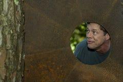 Όμορφο ώριμο άτομο στην τρύπα πιάτων σιδήρου, που κοιτάζει μακριά, για τη διαφήμιση στοκ φωτογραφία