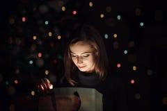 Όμορφο δώρο ανοίγματος γυναικών κοντά στο χριστουγεννιάτικο δέντρο στοκ φωτογραφία