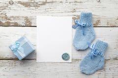 Όμορφο δώρο, κάλτσες μωρών ` s και κενή κάρτα στο άσπρο ξύλινο υπόβαθρο Επίπεδος βάλτε Στοκ Φωτογραφία