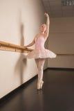 Όμορφο ballerina που στέκεται τη EN pointe μπάρα εκμετάλλευσης στοκ εικόνες με δικαίωμα ελεύθερης χρήσης